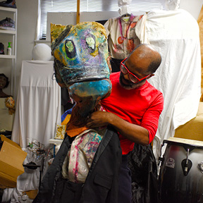 Afro American man inf red shirt and red glasses working on a colorful paper mache animal headhr
