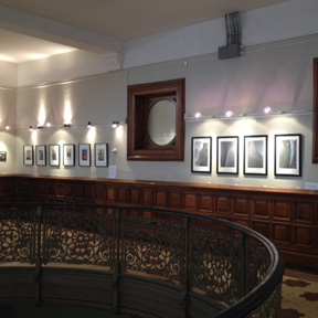 Rotunda Gallery wall with several pictures. Top portion of stair case visible