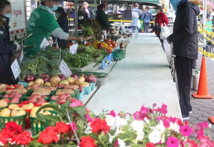 Jersey City Farmers Markets now open Long table pictured with flowers, apples, broccoli and tomatoes. A person is filling an order