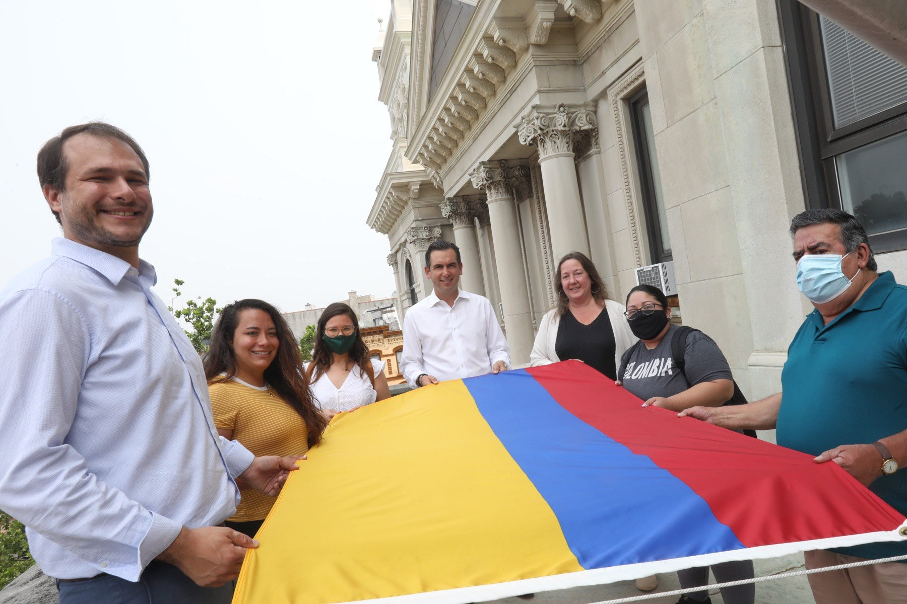 A group pf people hold the Colombian flag prior to raising. The flag consists of horizontal tricolor of yellow (double-width), blue and red with a white circle outlined in red and the coat of arms of Colombia defaced in the center.. The national flag of Colombia symbolizes Colombian independence from Spain, gained on July 20, 1810. It is a horizontal tricolor of yellow, blue and red.