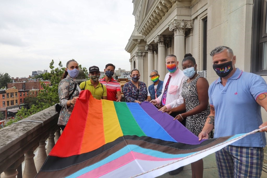 A large group of people hold the LGBTQ+ flag before it is raised. The rainbow flag is a symbol of lesbian, gay, bisexual, transgender, and queer (LGBT) pride and LGBT social movements The flag consists eight colors stripes, each color with its own meaning (hot pink for sex, red for life, orange for healing, yellow for sunlight, green for nature, turquoise for art, indigo for harmony, and violet for spirit).