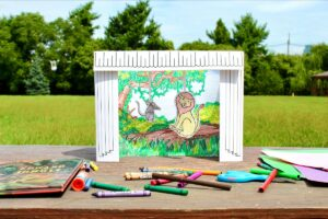 Outdoor Background Small paper stage with Curtain. Forest scene inside with animals. Stage is sitting on a picnic table with art supplies scattered in front of it