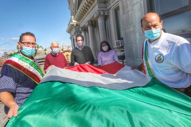 Italian flag raising ceremony 5 people hold the italian glag before it is raised