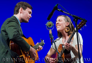 A woman and man guitar players performing