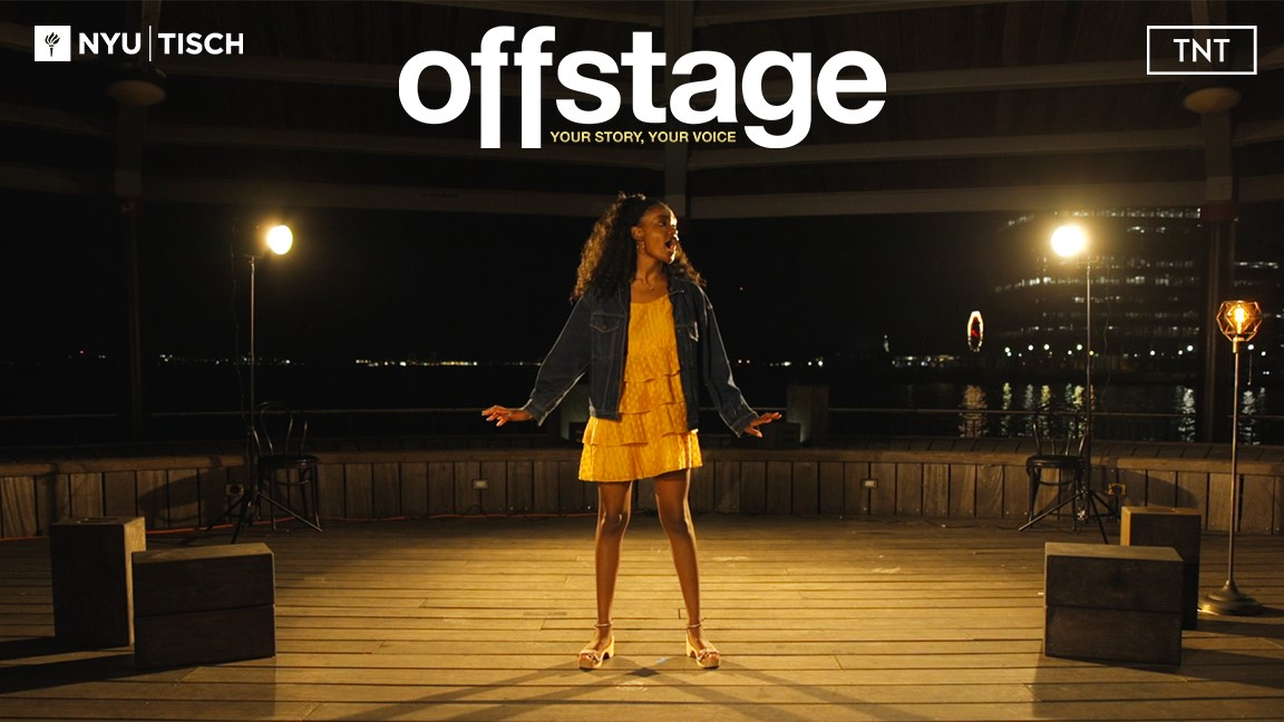 Offstage photo with black girl performing on stage. Wearing a tiered ruffle knee length dress with denim jacket