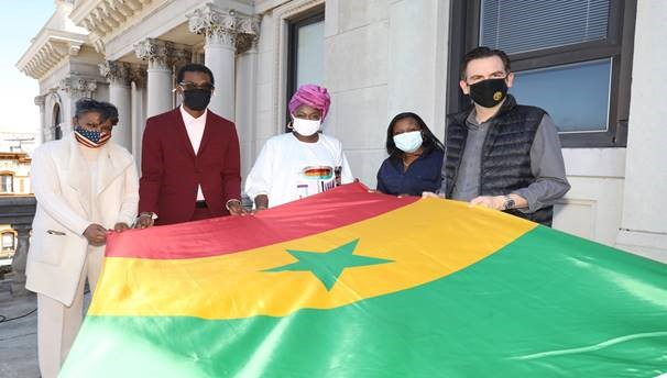 Mayor Steven Fulop and 4 others hold the Senegalese flag before it it raised. The flag is made up of three vertical stripes of green, yellow, and red with a green star in the center of the flag. The red stripe represents life, sacrifice, and the willingness of the people to fight against underdevelopment in Senegal. The yellow stripe represents wealth.