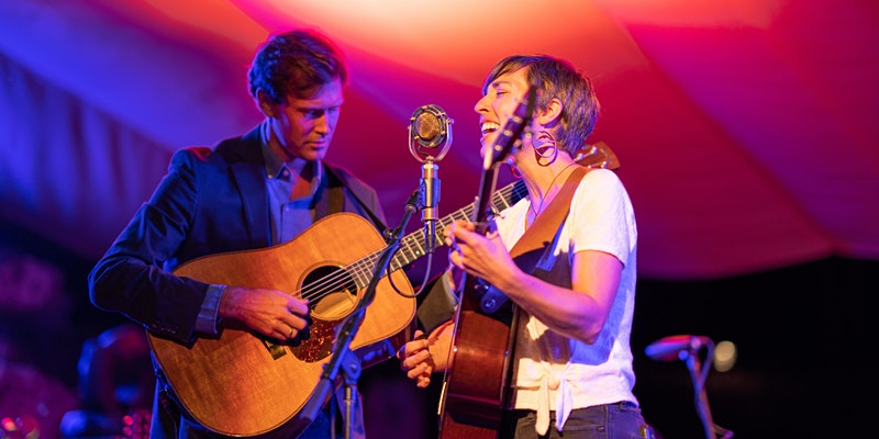 Man and woman guitar players performing on stage