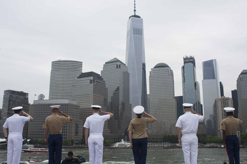 Military men standing in front of the New York Skyline saluting