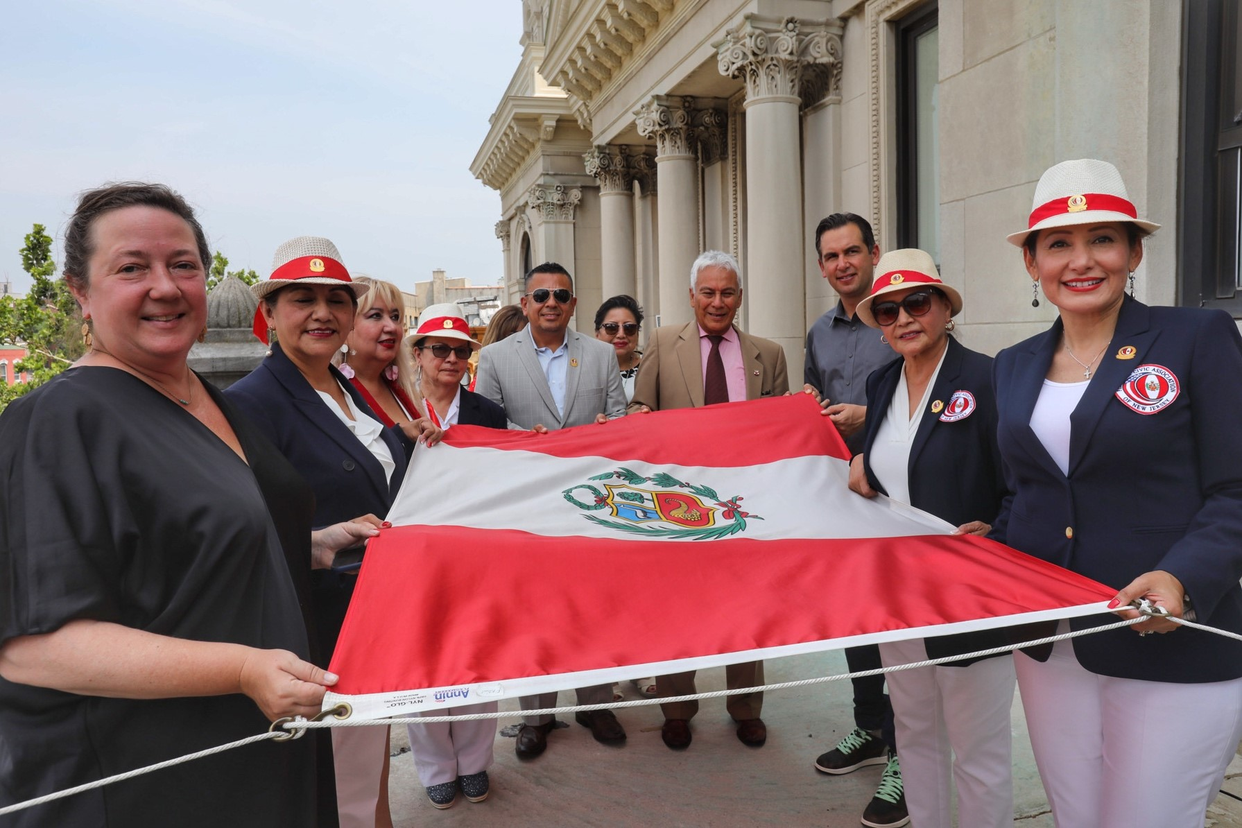 A group of people holding the flag before it is raised. the Peruvian flag The permanent national flag is of a vertical triband design, with red outer bands and a single white middle band. The color red represents blood shed for independence. White symbolizes purity and peace. The colors are believed to symbolize the lasting impact the Incas have had in the country.