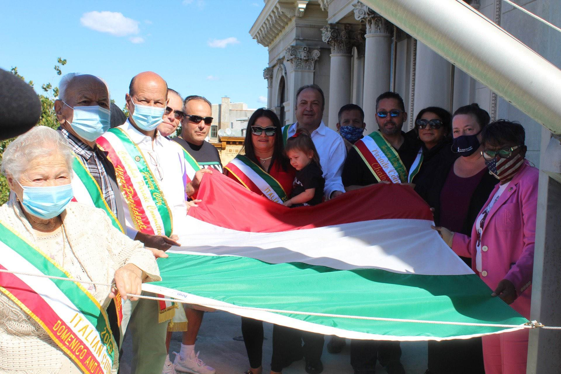 """A group of citizens hold the Italian before prior to raising. The flag is a vertical tricolor flag that is known in Italian as il Tricolore. It features three bands of equal sizes, with green located on the left """"hoist"""" side, white in the middle, and red on the right. The design is very similar to the tricolor flag of France from 1790. Wordage detailing event is underneath"""