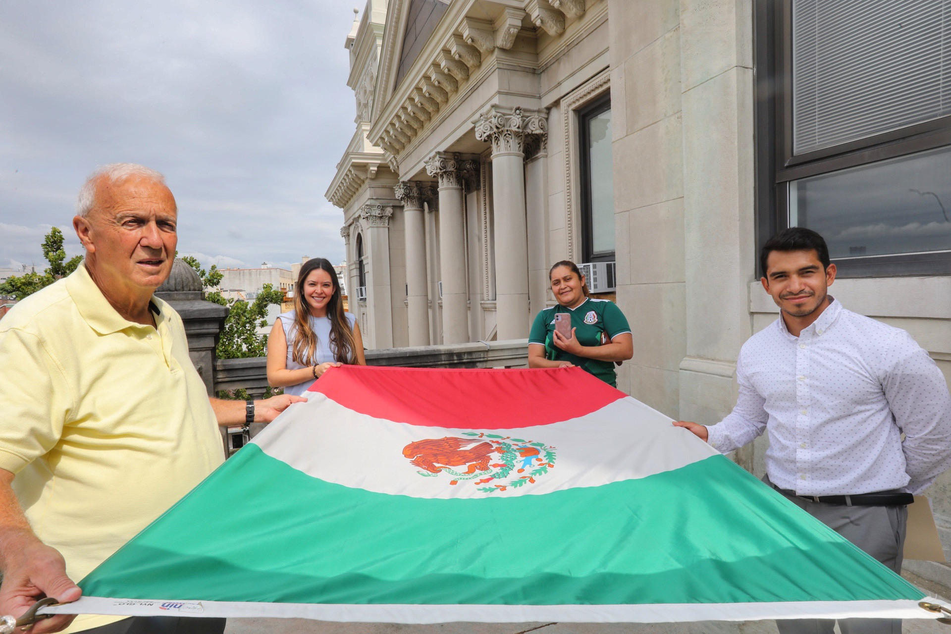 A group of people holding the flag before it is raised. The Mexican flag The Mexican flag appears against a cloud filled sky. The flag is designed with a tri a vertical tricolor of green, white and red with the National Coat of Arms centered on the white band.