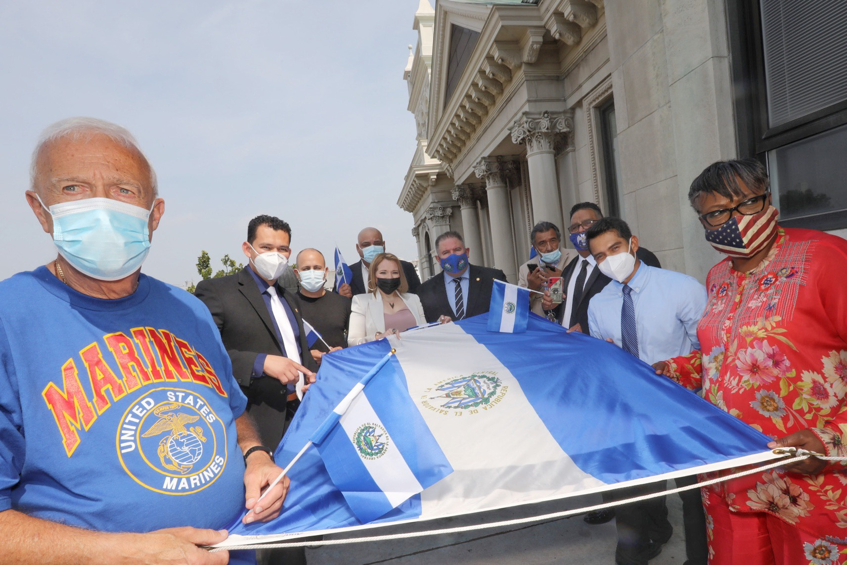 A group of citizens hold the flag before it is raised. The flag of El Salvador features a horizontal triband of cobalt blue-white-cobalt blue, with the coat of arms centered and entirely contained within the central white stripe. This design of a triband of blue-white-blue is commonly used among Central American countries.