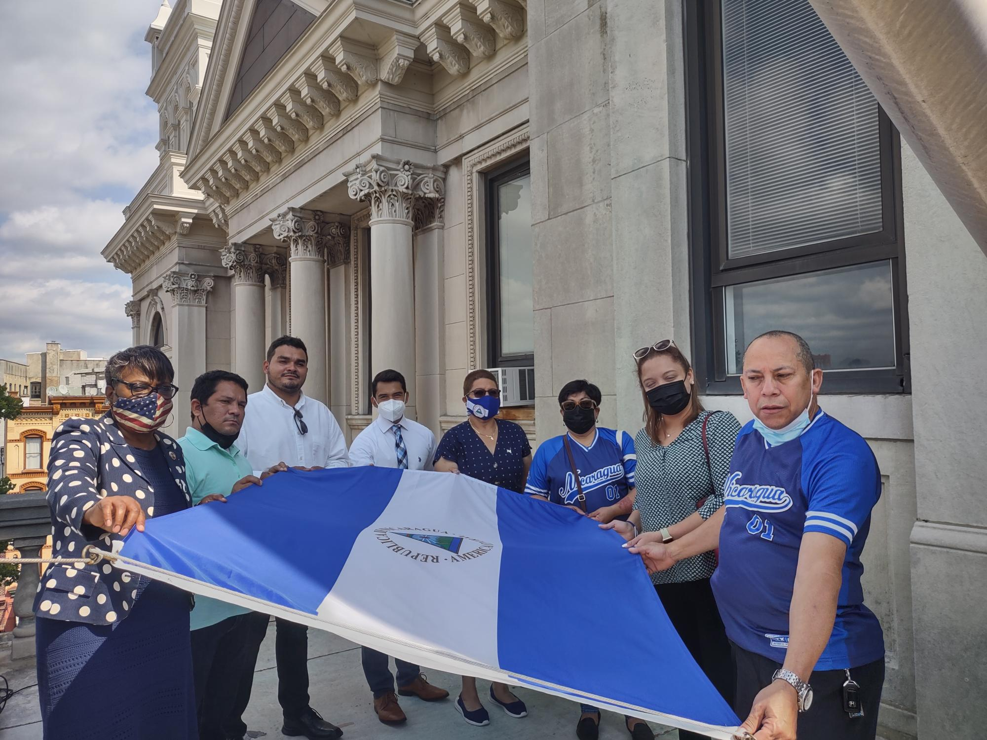 A group of citizens hold the flag of Nicaragua before it is raised. The flag is a bicolor with three horizontal bands of blue on the top and bottom and the white band in the middle. The country's National Coat of Arms is centered on the white band. The coat of arms features a triangle encircled by the words REPUBLICA DE NICARAGUA on the top and AMERICA CENTRAL on the bottom.