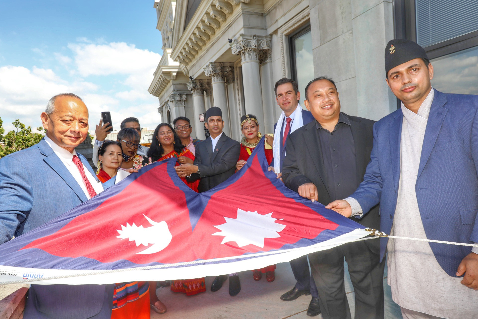 Several citizens are pictured holding the flag before it is raised The national flag of Nepal is a simplified combination of two single pennants. Its crimson red is the color of the rhododendron, the country's national flower. Red is also the sign of victory in war.