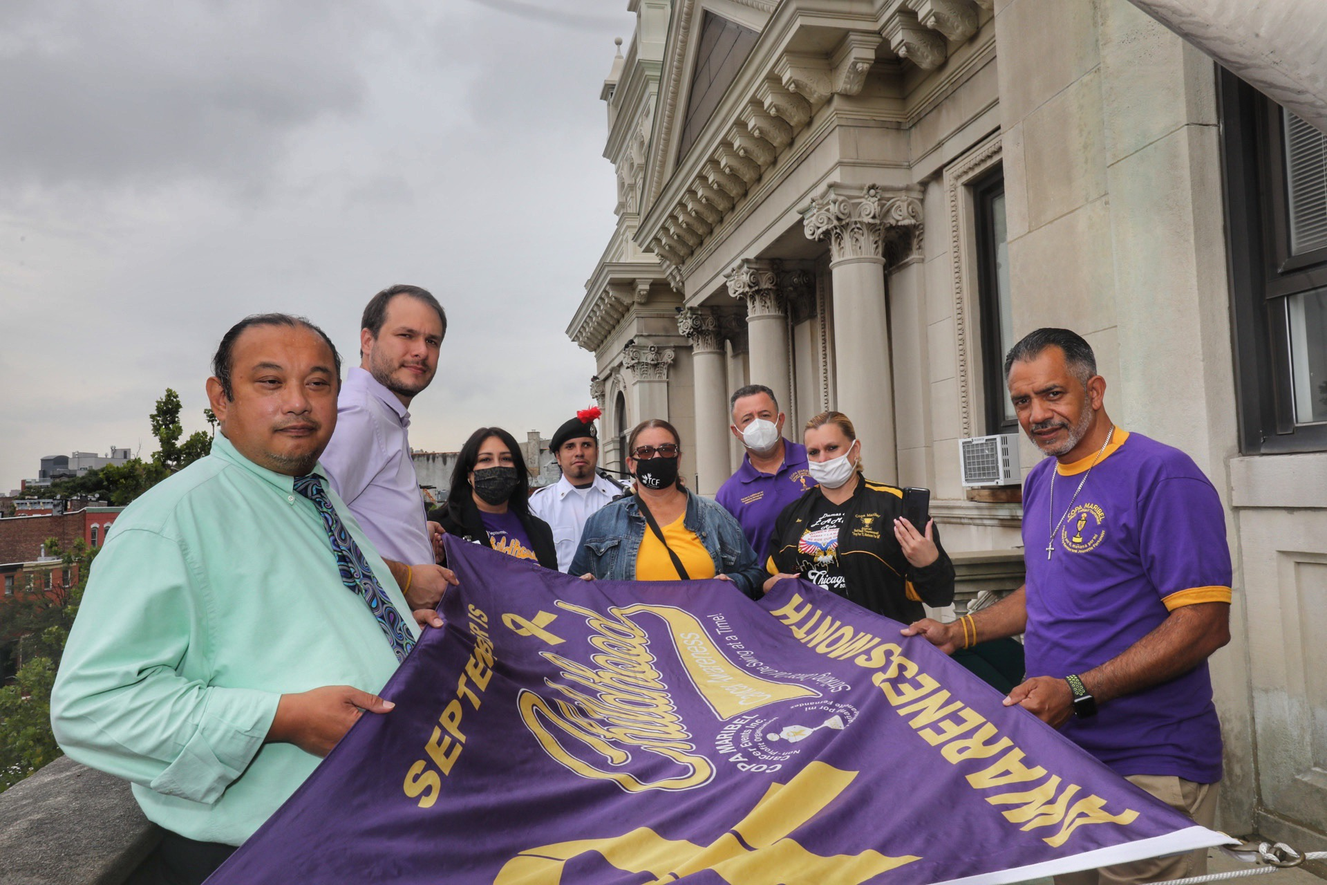 A group holds the flag before it is raised . It is deep purple with a gold ribbon.The international awareness symbol for Childhood Cancer is the gold ribbon. Unlike other cancer awareness ribbons, which focus on a singular type of cancer, the gold ribbon is a symbol for all forms of cancer affecting children and adolescents.